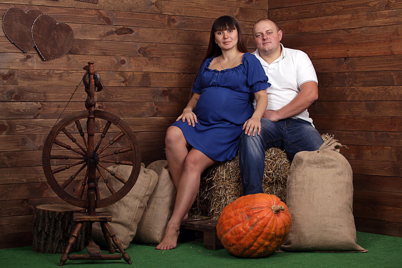 Фотосессия беременности на деревянном фоне в фотостудии