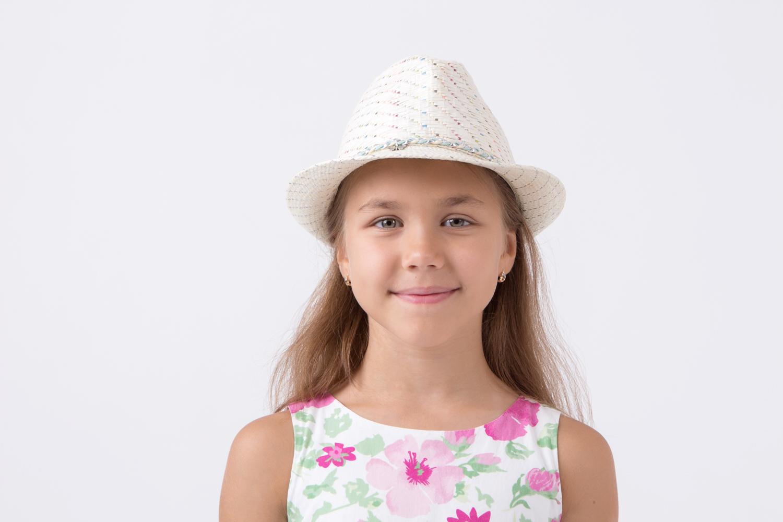 Дитя на белом фоне в белой шляпе